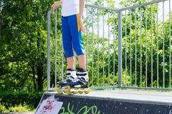 Las piernas de un patinador joven del rodillo en un cemento ramp Fotos de archivo libres de regalías