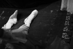 Las piernas de una bailarina que se sienta en el piso fotos de archivo