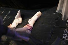 Las piernas de una bailarina que se sienta en el piso imagen de archivo