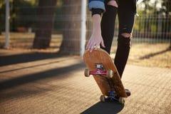 Las piernas de una muchacha del skater en zapatillas de deporte hacen un truco en un monopatín foto de archivo libre de regalías