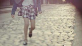 Las piernas de una niña en sandalias y una falda de tela escocesa corta que funcionamiento a lo largo del camino almacen de metraje de vídeo