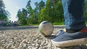 Las piernas del adolescente del muchacho golpean el balón de fútbol con el pie al equipo de fútbol de los niños al aire libre en  metrajes
