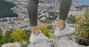 Las piernas del caminante de la mujer se colocan en roca del pico de monta?a metrajes