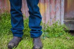Las piernas del granjero con las botas y los vaqueros Imagen de archivo libre de regalías