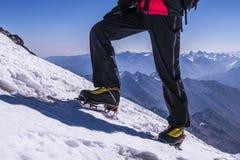 Las piernas del hombre en grampones vienen al top de la montaña Pies en botas del senderismo en el fondo del Cáucaso Fotos de archivo libres de regalías