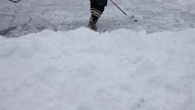 Las piernas del jugador de hockey en patines, palillo y duende malicioso en el hielo emergen en la pista de patinaje al aire libr almacen de video