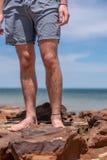 Las piernas del muchacho en la playa imagen de archivo