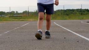 Las piernas del niño en los pantalones cortos y las zapatillas de deporte funcionados con en la rueda de ardilla en el primer del almacen de video