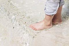 Las piernas del niño están en la corriente del agua clara Concepto ecol?gico Problemas de la falta de agua potable imagen de archivo