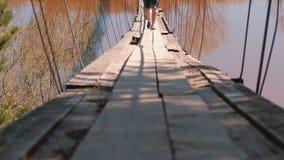 Las piernas del primer de la mamá, del papá y de la hija de la familia caminan en puente colgante viejo sobre el río metrajes