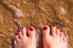 Las piernas del ` s de la mujer, los pies desnudos se colocan en la arena en la playa, hola el concepto agradable de las vacacion Imagen de archivo libre de regalías