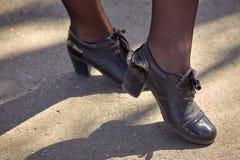 Las piernas del ` s de las mujeres en medias negras ennegrecen los zapatos en el asfalto imágenes de archivo libres de regalías