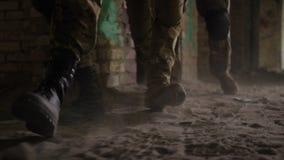 Las piernas del soldado en botas de combate del ejército caminan en el edificio almacen de metraje de vídeo