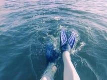Las piernas en aletas caen en el agua azul en el sol en un d?a de verano caliente fotografía de archivo