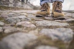 Las piernas en botas se colocan en los adoquines cubiertos de musgo viejos en la ciudad Fotos de archivo
