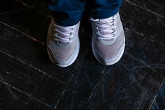 Las piernas en las zapatillas de deporte blancas están en el piso de entarimado negro fotos de archivo libres de regalías