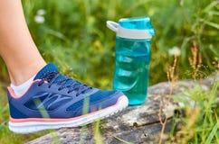 Las piernas en zapatillas de deporte de los deportes están en un pedazo de madera, cerca son una botella de los deportes con agua Fotografía de archivo