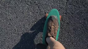 Las piernas en zapatillas de deporte están en un monopatín verde, metrajes