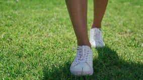 Las piernas femeninas delgadas en los zapatos blancos van derecho almacen de video
