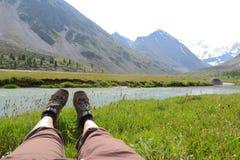 Las piernas femeninas en la hierba y las monta?as ajardinan en fondo fotografía de archivo libre de regalías