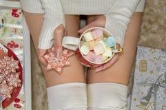 Las piernas femeninas, la muchacha están sosteniendo una taza de melcochas Primer Humor de la Navidad imagenes de archivo