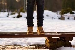 Las piernas femeninas se están colocando en banco en día soleado del invierno Fondo borroso de los rayos de la nieve y de la pues imagenes de archivo