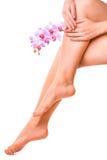 Las piernas femeninas y la manicura rosada con la orquídea florecen Fotografía de archivo