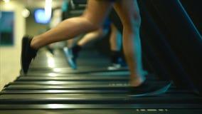 Las piernas masculinas en zapatillas de deporte corren en un orbitrek-simulador almacen de metraje de vídeo
