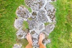 Las piernas masculinas se colocan en un camino y una hierba rocosos Fotos de archivo libres de regalías