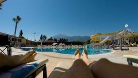 Las piernas mienten en el ocioso cerca de la piscina almacen de metraje de vídeo