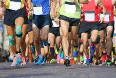 las piernas musculares de un gran número de corredores durante deportes compiten con Foto de archivo