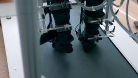 Las piernas pacientes del ` s en enlaces de una máquina del entrenamiento están caminando lentamente a lo largo de la pista corri almacen de metraje de vídeo