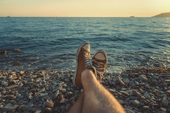 Las piernas para hombre en zapatillas de deporte en fondo del mar pintoresco ajardinan concepto relajante de la playa del verano Imagenes de archivo