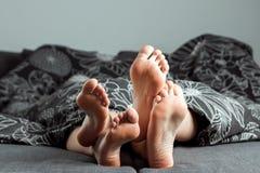 Las piernas, pies de un par en amor se est?n pegando hacia fuera de debajo la manta El d?a o la historia de amor de la tarjeta de imagen de archivo