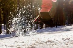 Las piernas que despiden a las muchachas, nieve vuelan relucir en el sol Foto de archivo libre de regalías