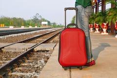 Las piernas turísticas del viajero casual se colocan en ferrocarril con una maleta roja Imagenes de archivo