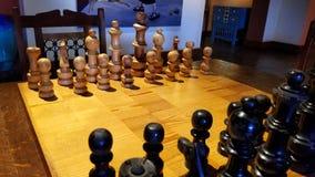 Las piezas de ajedrez de madera en la posición de salida, alistan para el juego imagen de archivo