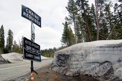 Las pilas de la nieve en lado del camino con tráfico señal adentro el moun de Sierra Nevada Imagen de archivo