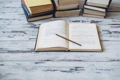 Las pilas de libros con un libro abren y dibujan a lápiz lzing en sus páginas Imagen de archivo