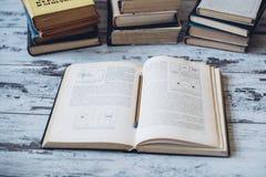 Las pilas de libros con un libro abren y dibujan a lápiz lzing en sus páginas Imagen de archivo libre de regalías