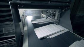 Las pilas de papel con el texto impreso se están moviendo a lo largo de la banda transportadora almacen de metraje de vídeo