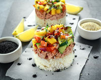 Las pilas del sushi del atún con el mango, pepino, salsa de los tomates sirvieron con el vinagre balsámico, semillas de sésamo de Imagenes de archivo