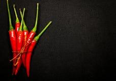 Las pimientas de chile rojo en fondo negro, chile picante fresco sazonan con pimienta Imagenes de archivo