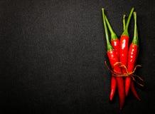 Las pimientas de chile rojo en fondo negro, chile picante fresco sazonan con pimienta Foto de archivo libre de regalías