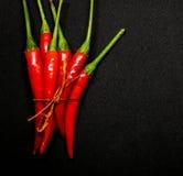 Las pimientas de chile rojo en fondo negro, chile picante fresco sazonan con pimienta Fotografía de archivo libre de regalías