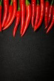 Las pimientas de chile rojo en fondo negro, chile picante fresco sazonan con pimienta Imágenes de archivo libres de regalías