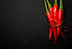 Las pimientas de chile rojo en fondo negro, chile picante fresco sazonan con pimienta Foto de archivo