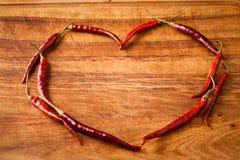 Las pimientas de chile rojo secadas en corazón forman en corte rústico, oscuro de madera Foto de archivo