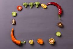 Las pimientas de chiles con los tomates y el bróculi en fondo gris componen el marco foto de archivo libre de regalías