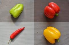 Las pimientas verdes amarillas rojas en un fondo dividieron en zonas de diversos colores foto de archivo libre de regalías